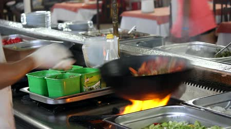 preparar : Cook in a restaurant preparing food in a wok