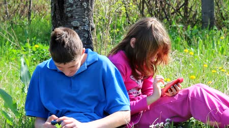 vztahy : Teenagers having fun with their mobile phones in nature Dostupné videozáznamy