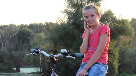 portre : Girl speaks on a mobile phone while sitting on bicycles in the countryside