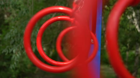 expectativa : Gymnastics rings swinging on the sports ground. HD slowmotion