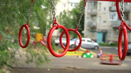 desfocado : Gymnastic rings on the playground in the yard. Unfocused children on background