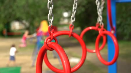 mateřská škola : Gymnastic rings on the playground in the yard. Unfocused children on background