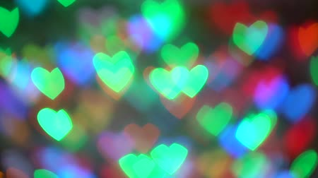 Garland burn and flicker in soft defocused bokeh. Blurred bokeh in form of hearts of New Years flickering garlands. Festive mood. Christmas or New Year background