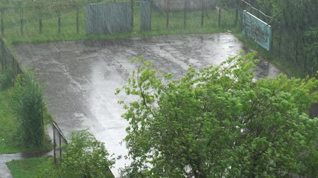 meteorological : Summer heavy rain in city. Top view on green courtyard and playground. 4K video
