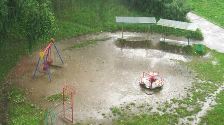 srážky : Summer heavy rain in city. Top view on green courtyard, playground and puddle. 4K video