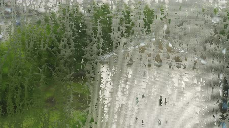 nedvesség : Drops of water, like lenses, on mosquito net. Summer pouring rain in city. 4K video