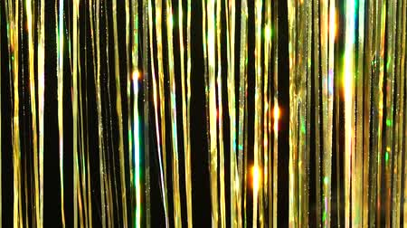 Gold rain from tinsel. Dynamic background in shining lights and sparkling particles. Beautiful gold background with shiny yellow glitter sparkles. Festive mood. Christmas or holiday theme