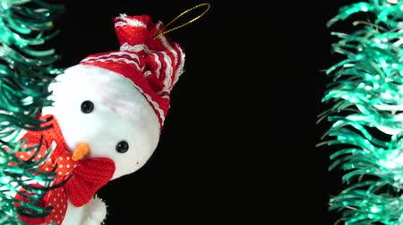 Cute snowman in red hat and bow looks at you from scene. Christmas greeting on black background. Festive mood. New Year or holiday theme Archivo de Video