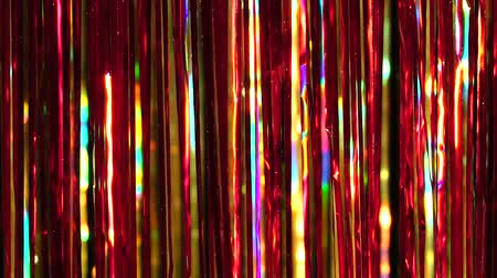 Gold and Red rain from tinsel. Dynamic background in shining lights and sparkling particles. Beautiful background with shiny glitter sparkles. Festive mood. Christmas or holiday theme