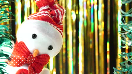 Cute snowman in red hat and bow looks at you from scene. Christmas greeting on gold background. Festive mood. New Year or holiday theme