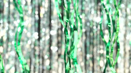 díszítés : Green tinsel on silver bokeh background. Beautiful dynamic background in shining lights and sparkling particles. Festive mood. Christmas or holiday theme.