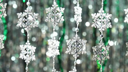Close up shot, focused on decorative snowflake in foreground. Magic abstract shiny background with colored defocused bokeh. Festive mood. Christmas or holiday theme. Video