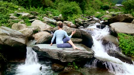 himalaya : Woman doing Ardha matsyendrasana asana outdoors