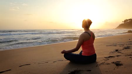 mento : Woman doing yoga oudoors at beach - Padmasana lotus pose Filmati Stock