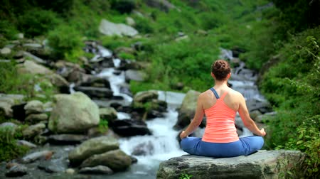 cross training : Woman meditating at tropical waterfall