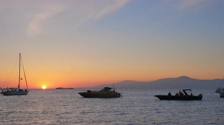 venedik : Sunset in Mykonos, Greece with and yachts in the harbor Stok Video