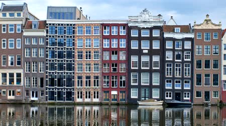 Medieval houses at Amsterdam canal at Damrak pier on sunset. Netherlands