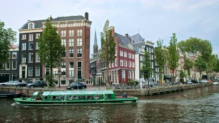 Amsterdam canal with boats, bridge and medieval houses