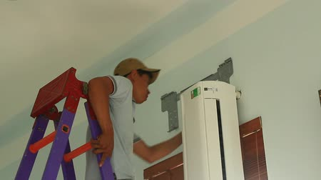 elektryk : Haiduong, Vietnam, may 31, 2015: worker installing air conditioners is in the house Wideo