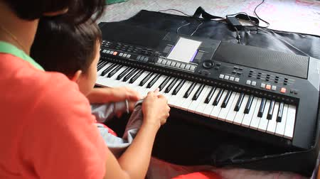 плохо : teacher teach the boy playing organ on November, 25, 2014 in Hai Duong, Vietnam.