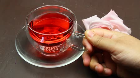 homeopatia : Pouring herbal tea in a cup and lighting candles.
