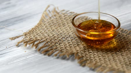 sirup : Honey pouring in a small bowl on a burlap cloth.
