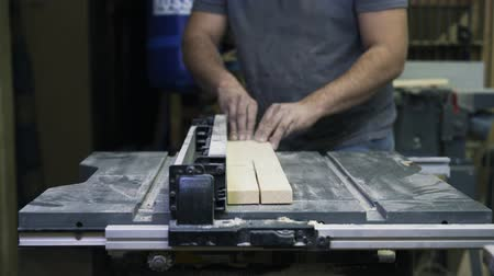 paneling : A craftsman is working with wood using a special machine. sawing a bar. Real time shot. Industrial tool.