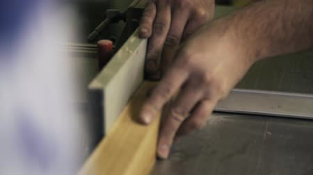 paneling : A craftsman is working with wood using a special power tool. Sanding a wooden bar. Real time close up shot.