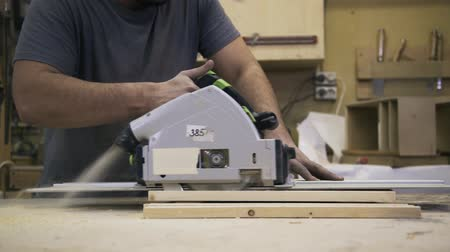 paneling : A craftsman is sawing a wooden bar using an industrial Circular Saw. Real time shot Stock Footage