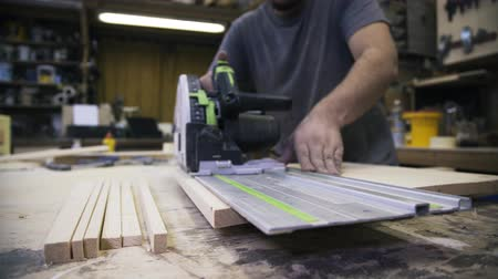 paneling : A craftsman is sawing a wooden bar using a power saw. Real time shot