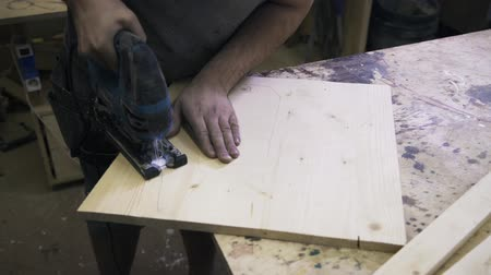bandsaw : A craftsman is sawing a wooden bar using a fretsaw. Real time close up shot. Stock Footage