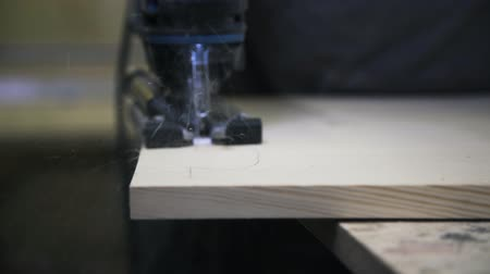 paneling : A craftsman is sawing a wooden bar using a power fretsaw. Real time close up shot.