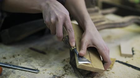 restorer : A young attractive carpenter is restoring the wood element of some furniture.