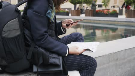 długi : Unrecognizable young woman sitting near a fountain in a Valencia street in Spain and web surfing while holding a map. Left to right pan real time close up shot