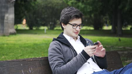 trancado : Side view of a young man in glasses web surfing in a park in Valencia, Spain. He is sitting on a bench. Locked down real time medium shot