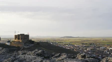 tartomány : Pan shot of windmills and a castle, Consuegra, Toledo province, Castilla la Mancha, Spain. Left to right pan real time medium shot Stock mozgókép