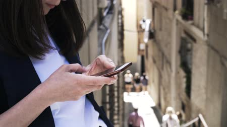 middle : Close up of an unrecognizable young businesswoman texting from her smartphone in a Toledo street. People in the background. Handheld real time close up shot Stock Footage