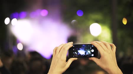 félrebeszél : Close up of girl s hands with a mobile phone filming a music festival in Toledo, Spain at night. Locked down real time medium shot Stock mozgókép