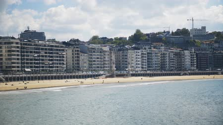 basque : Beautiful beach. People are having fun in San Sebastian, a resort town on the Bay of Biscay in Spain s mountainous Basque Country. Locked down panoramic real time medium shot