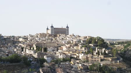 iberian : Panoramic view of Toledo. Beautiful historic buildings made of white stone, cars are riding on a mountain road. Left to right pan real time establishing shot