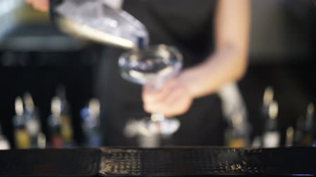 iceberg : Close up of an unrecognizable woman bartender putting ice cubes into a cocktail glass and placing it on the counter. Handheld real time close up shot