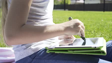 implementation : Close up of a girl drawing on a tablet computer sitting on a lawn in a park on a summer day. Handheld real time close up shot