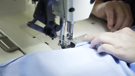 hímzés : Close up of an unrecognizable semstress hands sewing a blue shirt at a factory. She is using a sewing machine. Handheld real time close up shot