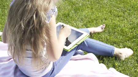 implementation : Rear view of a blonde girl drawing on a tablet computer sitting on a lawn in a park on a summer day. Handheld real time close up shot