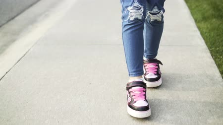 inline : Front view of an unrecognizable girl wearing blue jeans roller skating in a park. Concept of a summer vacations. Handheld real time close up shot Stock Footage