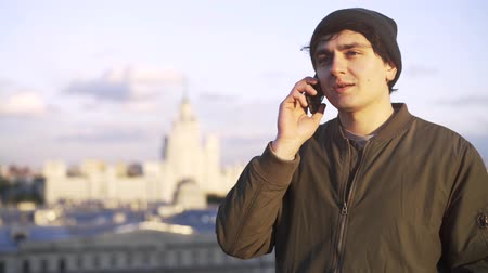 khaki : Young man wearing a khaki jacket and a beanie is talking on his smartphone while standing on a roof of a building. Locked down real time medium shot