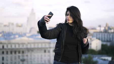 trancado : Young woman with long hair wearing black clothes is standing on a roof of a building in a city and taking a selfie. Locked down real time medium shot