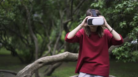 trancado : Young woman wearing a red sweater is using VR glasses while being at a park near large tree. Locked down real time close up shot Stock Footage