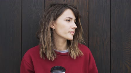 trancado : Young woman wearing a red sweater is drinking coffee to go while standing near a wooden wall. Locked down real time close up shot Stock Footage