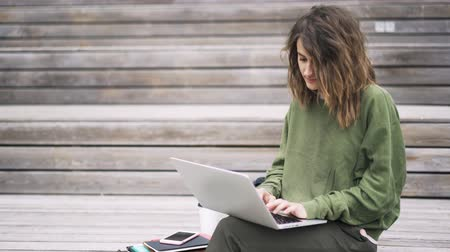 ネットブック : Side view of a beautiful young woman wearing a green sweatshirt sitting on the stairs outside and typing at her laptop keyboard. Locked down real time establishing shot
